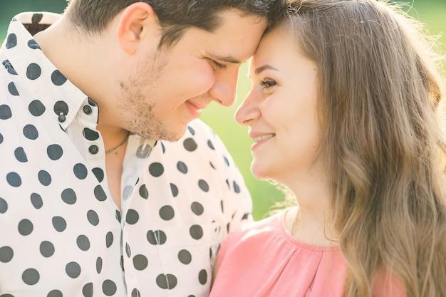 Les futurs parents heureux penchent la tête ensemble et sourient. fermer.