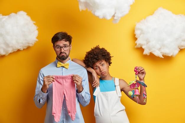 Les futurs parents tristes et ennuyés attendent bébé, achètent des vêtements et un berceau mobile pour nouveau-né, posent ensemble contre un mur jaune, des nuages duveteux au-dessus de la tête. les futurs père et mère se préparent à la parentalité