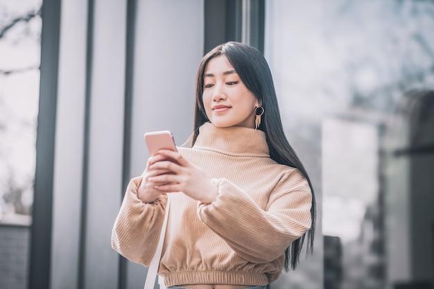 Gadget. jolie jeune femme asiatique tenant un smartphone dans ses mains