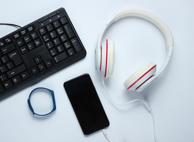 Gadgets et accessoires numériques modernes. ordinateur portable, smartphone, bracelet intelligent, écouteurs sur fond blanc. vue de dessus.