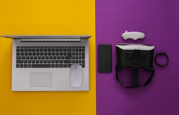 Gadgets et appareils de jeunesse modernes sur fond jaune violet. vue de dessus. mise à plat