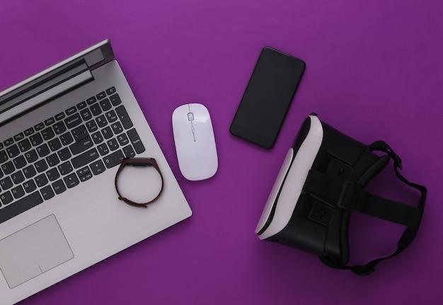Gadgets et appareils de jeunesse modernes sur fond violet. vue de dessus. mise à plat