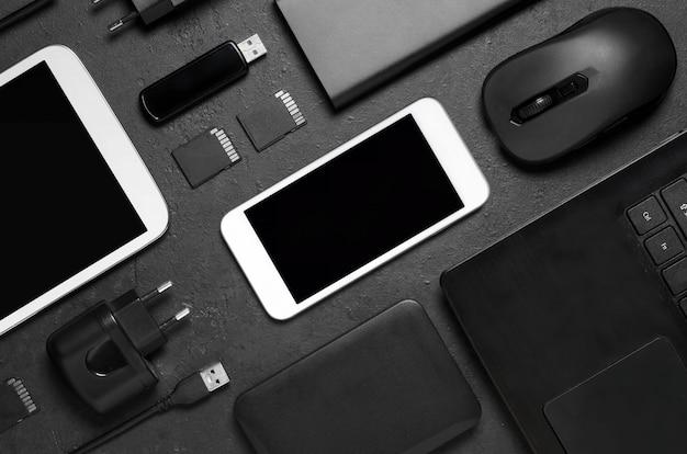 Gadgets électroniques sur fond de béton noir. concept d'accessoires pour une entreprise prospère. mise à plat.