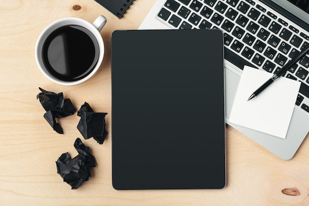Gadgets électroniques et fournitures de bureau sur une table en bois