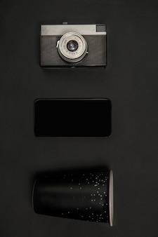 Gadgets et lunettes. composition monochrome élégante et tendance de couleur noire sur le mur du studio. vue de dessus, mise à plat.