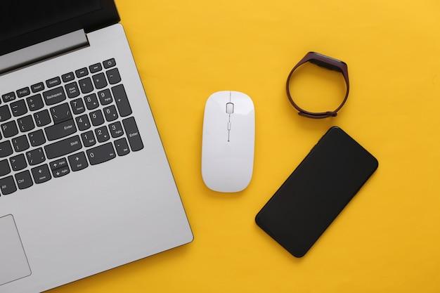 Gadgets modernes. ordinateur portable avec souris pc, smartphone, bracelet intelligent sur fond jaune. vue de dessus. mise à plat