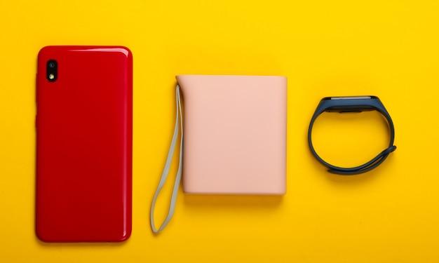 Gadgets modernes. smartphone et bracelet intelligent, batterie externe sur jaune