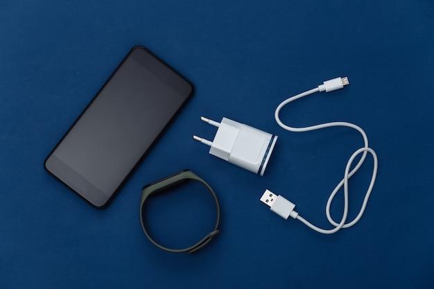 Gadgets modernes. smartphone, chargeur, bracelet intelligent sur fond bleu classique. couleur 2020. vue de dessus