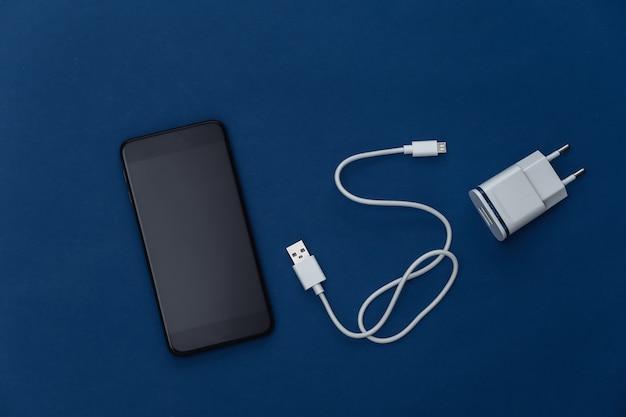 Gadgets modernes. smartphone, chargeur sur fond bleu classique. couleur 2020. vue de dessus