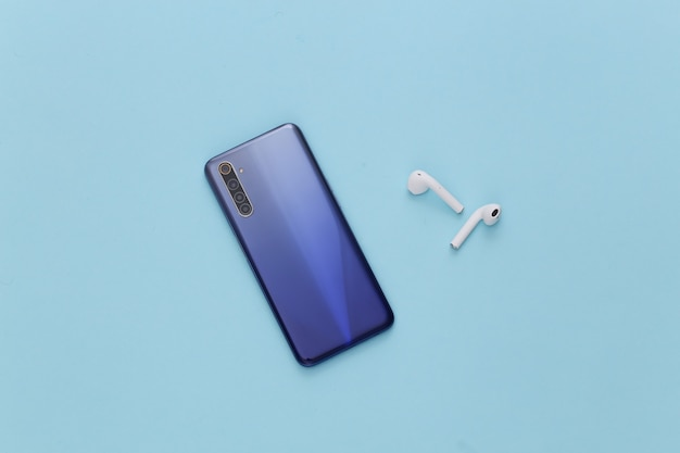 Gadgets modernes. smartphone moderne avec écouteurs sans fil sur bleu