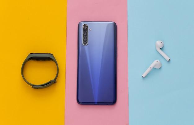Gadgets modernes. smartphone moderne avec écouteurs sans fil et bracelet intelligent sur table colorée. mise à plat