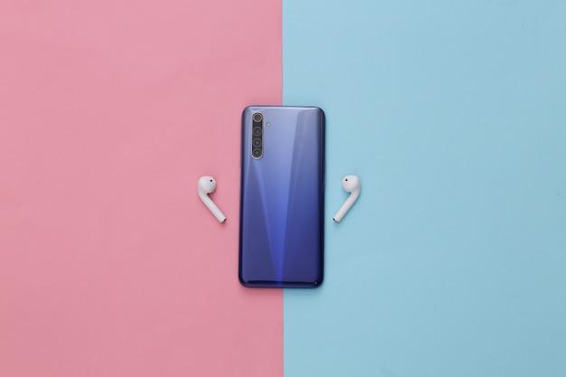 Gadgets modernes. smartphone moderne avec écouteurs sans fil sur pastel bleu rose