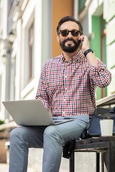 Gadgets numériques. enthousiaste homme agréable parlant au téléphone et utilisant un ordinateur portable à l'extérieur