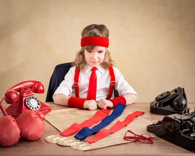 Gagnant enfant homme d'affaires au bureau. succès, leader et concept d'entreprise