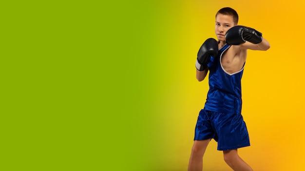 Gagnant. formation de boxeur professionnel adolescent en action, mouvement isolé sur fond dégradé à la lumière du néon. coup de pied, boxe. concept de sport, mouvement, énergie et mode de vie sain et dynamique. prospectus