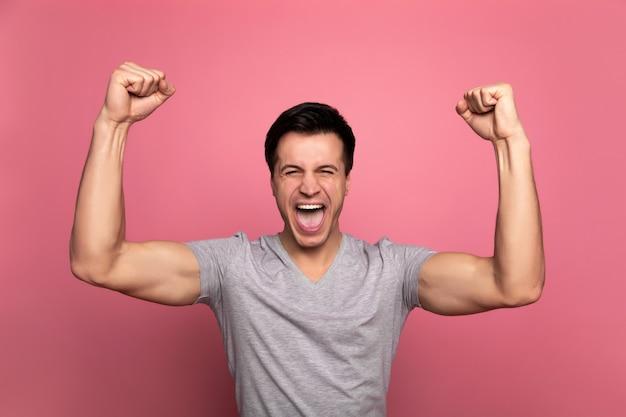 Le gagnant. homme athlétique, qui crie, tout en tenant ses poings au-dessus de sa tête.