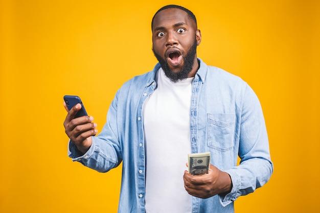 Gagnant! jeune homme afro-américain riche en t-shirt décontracté tenant des billets d'un dollar en argent et un téléphone mobile avec surprise