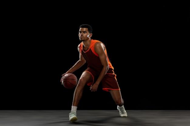 Gagnant. jeune joueur de basket-ball afro-américain déterminé, s'entraînant en action, mouvement isolé sur fond noir. concept de sport, mouvement, énergie et mode de vie sain et dynamique.