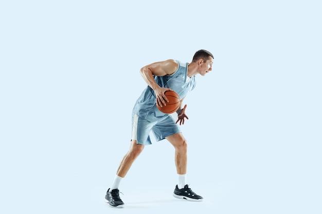 Gagnant. jeune joueur de basket-ball caucasien de l'équipe en action, mouvement en saut isolé sur bleu.