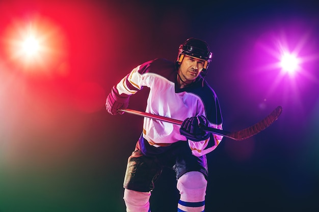Gagnant. joueur de hockey masculin avec le bâton sur la glace et le mur de couleur néon foncé. sportif portant des équipements, casque pratiquant. concept de sport, mode de vie sain, mouvement, bien-être, action.
