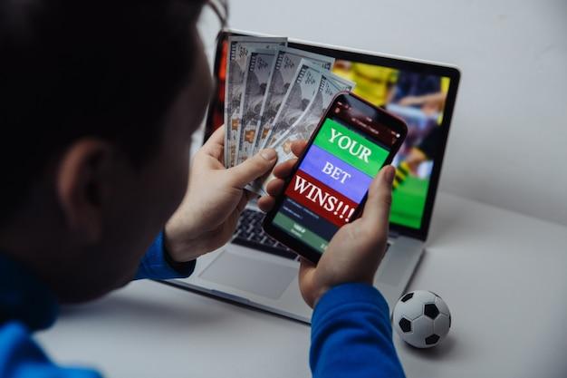 Gagnant masculin chanceux au football pari avec de l'argent en dollars et téléphone en mains. le pari gagne.