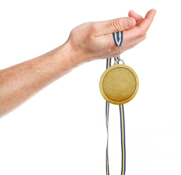 Gagnant de la médaille d'or dans la main. sur un mur blanc.