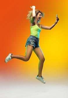 Gagnant. portrait d'une jeune femme caucasienne sautant sur fond de studio dégradé au néon. beau modèle féminin bouclé dans un style décontracté. concept d'émotions humaines, expression faciale, jeunesse, ventes, publicité.