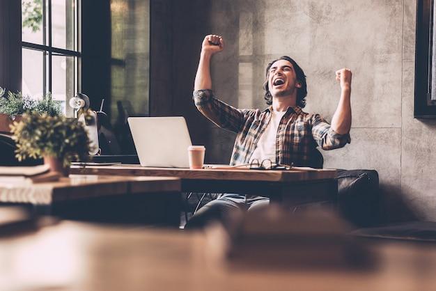 Gagnant de tous les jours. gai jeune homme en tenue décontractée gardant les bras levés et l'air heureux alors qu'il était assis au bureau au bureau