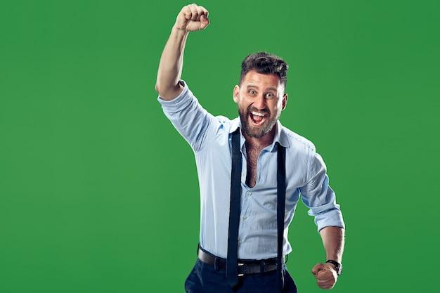 Gagner le succès homme heureux célébrant être un gagnant. image dynamique du modèle masculin caucasien sur le mur vert. victoire, concept de plaisir. concept d'émotions faciales humaines.