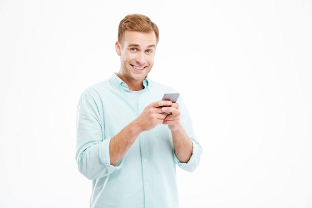 Gai beau jeune homme d'affaires debout et utilisant un smartphone sur un mur blanc