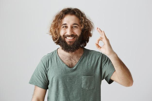 Gai beau mec du moyen-orient montre un geste correct, garantit la qualité