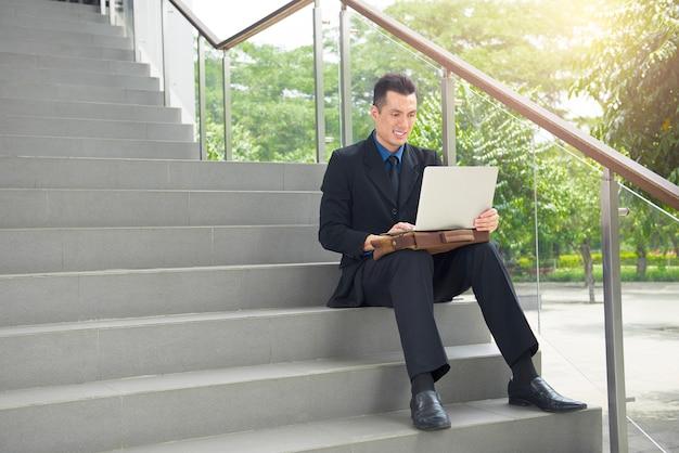 Gai homme d'affaires asiatique avec ordinateur portable
