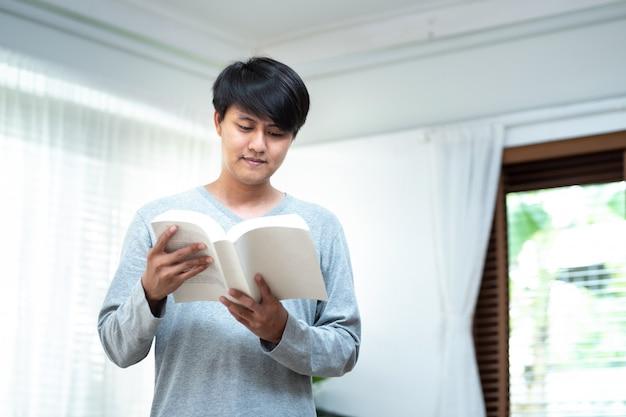 Gai homme asiatique robe en tenue décontractée se détendre dans la main du café tenir le livre regarder la caméra pour la recherche de données et l'auto-amélioration. opportunité d'éducation et de bourse. concept de la journée mondiale du livre.