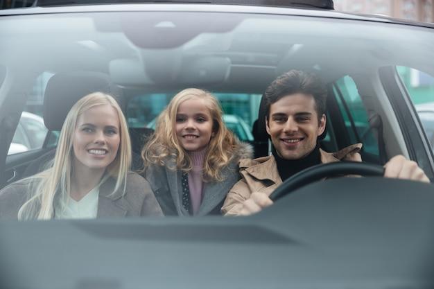 Gai homme assis dans la voiture avec sa femme et sa fille