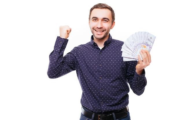 Gai homme barbu en chemise à carreaux tenant des billets d'un dollar sur un mur blanc