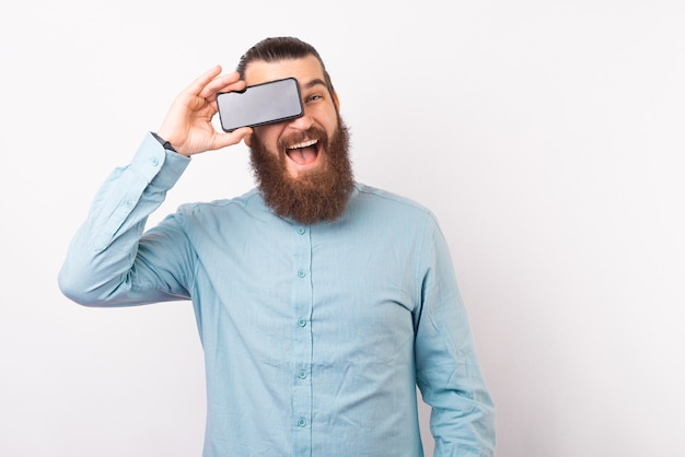 Gai homme barbu en tenue décontractée smartphone sur ses yeux et souriant