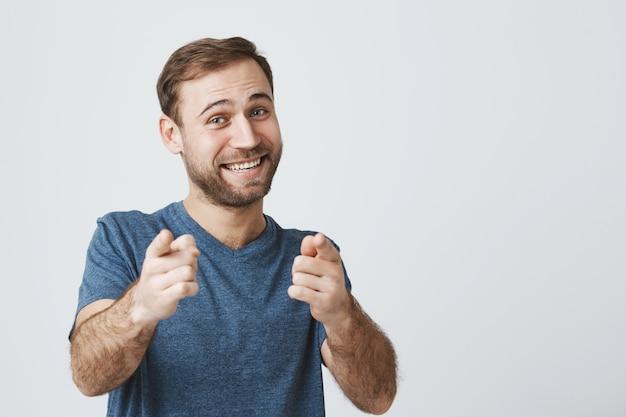 Gai homme barbu vous félicite, pointant l'appareil photo du doigt