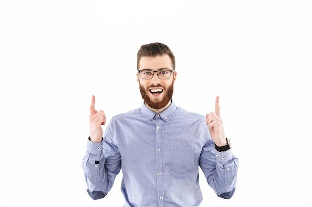 Gai homme élégant barbu à lunettes pointant vers le haut et regardant