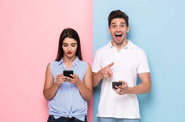 Gai, homme et femme, dans, tenue décontractée, tenue, smartphones, isolé, sur, mur coloré