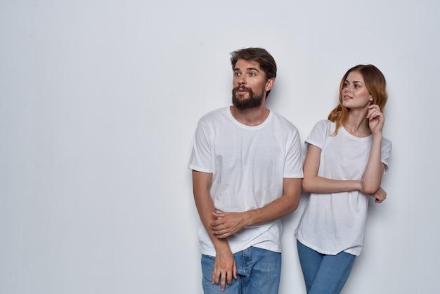Gai homme et femme en t-shirts blancs et jeans design studio fond clair