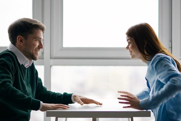 Gai homme et femme à la table bavardant café de rencontres