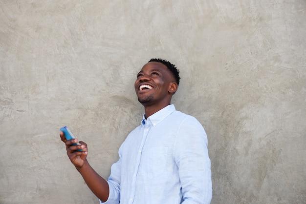 Gai, jeune, africain, téléphone portable, debout, mur