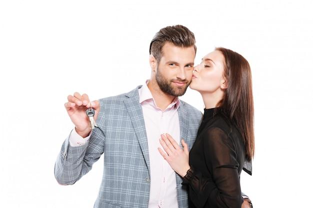 Gai jeune couple d'amoureux tenant les clés.