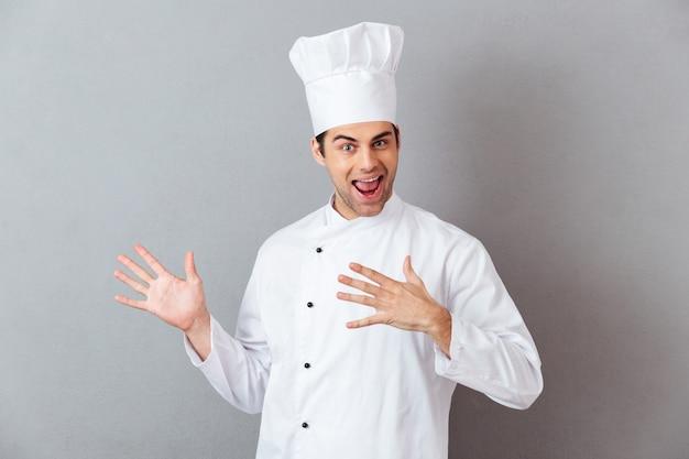 Gai jeune cuisinier en uniforme montrant la surface.
