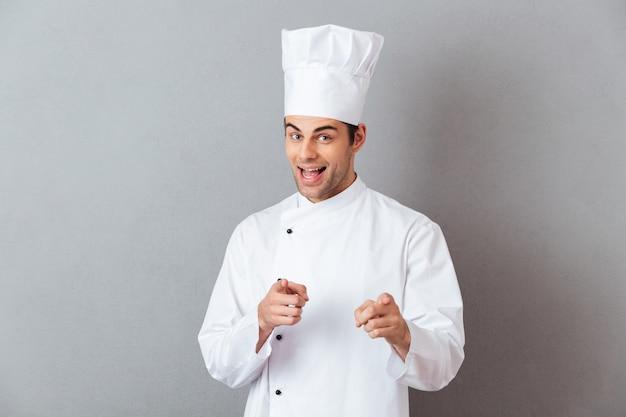 Gai jeune cuisinier en uniforme pointant vers vous.