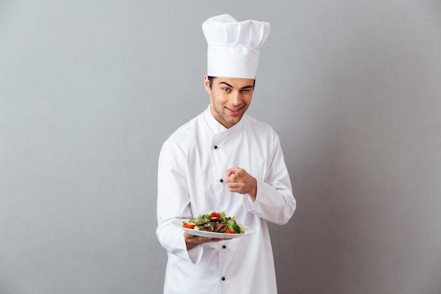 Gai jeune cuisinier en uniforme tenant une salade pointant vers vous.