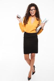 Gai jeune femme d'affaires africaine avec des dossiers et marche de téléphone mobile