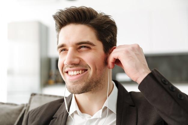 Gai jeune homme d'affaires dans la musique d'écoute à domicile