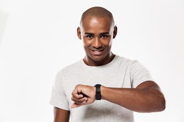 Gai jeune homme africain à l'aide de la montre.