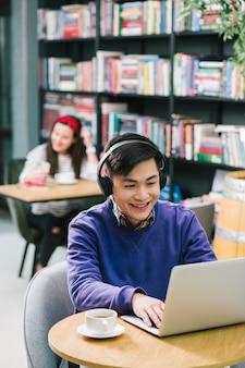 Gai jeune homme asiatique assis dans une bibliothèque avec des écouteurs sur la tête et regardant l'écran. tasse de café sur sa table